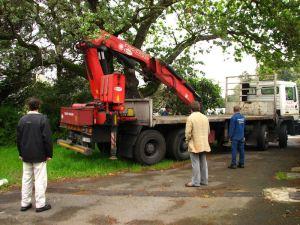 Crane truck reversing down the lane
