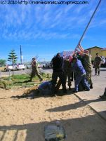Everyone lends a hand to raise the flagpole into position
