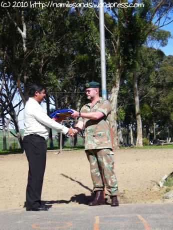 Lt Col Johan Conradie hands the national flag and a certificate of friendship to Mr Neil September