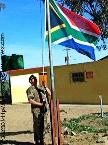 Warrant Officer First Class Stephen Jordaan solemnly raises the national flag