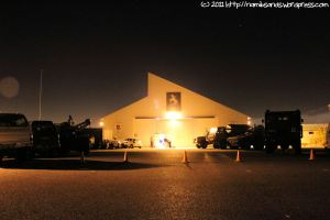 The military vehicles on display outside the hangar create the right atmosphere