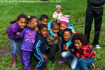 A bunch of playful kids posing for a group photo