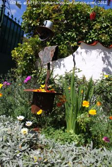 An unusual rustic metal sculpture welcomes visitors to the little cottage garden with its masses of colourful flowers