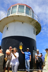 Richard bravely ignores the milling tourists to pose with Flat Kathy in front of the old lighthouse at Cape Point