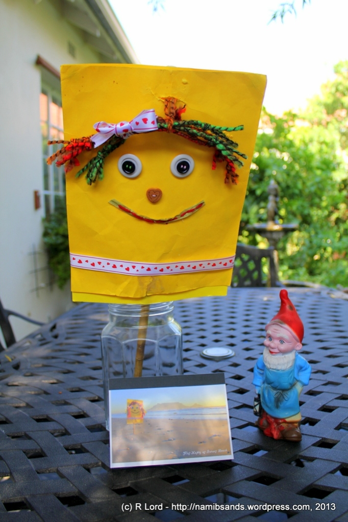Flat Kathy and Gilbert the Gnome admire the beautiful booklet of postcards