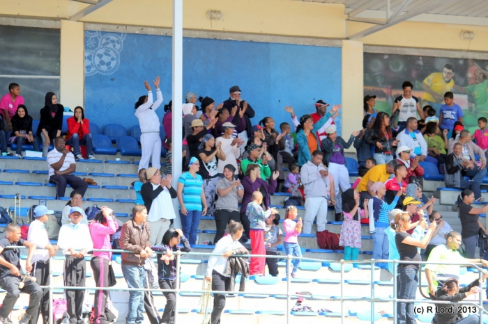 Cheering spectators on the grandstand leap to their feet whenever their school team is announced