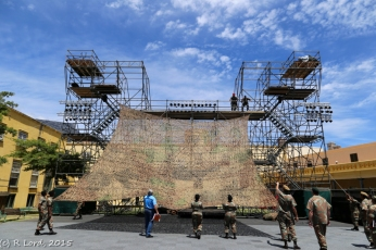 Camo netting is raised in front of the scaffolding
